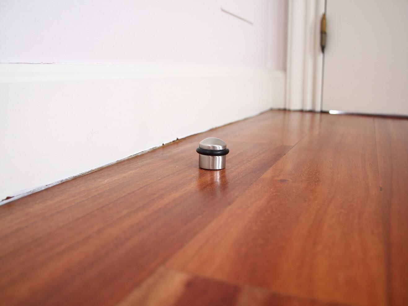 Tope de puerta sobre suelo de madera